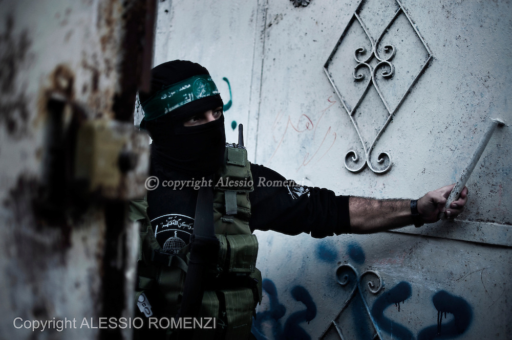 Gaza City: A gunman from the Ezzedine al-Qassam Brigades, the armed wing of Hamas, guards the door of the house of their late leader Ahmed Jaabari, as mourners visit to pay their condolences to his family. November 22, 2012. ALESSIO ROMENZI