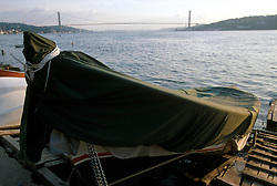 TURKEY ISTANBUL JUL02 - A fishingboat lies moored at Cengelköy on the Asian side of the Bosphorus Strait. In the background is the first Bosphorus bridge, built in 1974. Is is the fourth largest bridge in the world and connects the European and Asian parts of Istanbul and is one of the most heavily used traffic ateries in Turkey...jre/Photo by Jiri Rezac..© Jiri Rezac 2002..Contact: +44 (0) 7050 110 417.Mobile:   +44 (0) 7801 337 683.Office:    +44 (0) 20 8968 9635..Email:     jiri@jirirezac.com.Web:     www.jirirezac.com