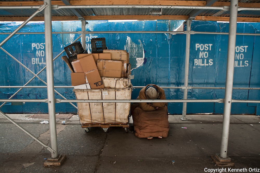 A homeless person sleeps next to a cart filled with all of their possessions under scaffolding in front of a construction site on 57th Street in midtown Manhattan.