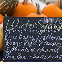 Winter squash and pumpkins at a farmers market.