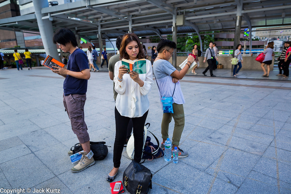 """29 MAY 2014 - BANGKOK, THAILAND:  People stand in a circle and read """"1984"""" as a protest against the coup. About eight people gathered at the Chong Nonsi intersection in Bangkok to silently read George Orwell's """"1984"""" and other books about civil disobedience. The protests are based on the """"Standing Man"""" protests that started in Turkey last summer. Authorities made no effort to stop the protest or interfere with the people who were reading.  PHOTO BY JACK KURTZ"""