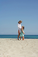 Mother and daughter (5-6) standing face to face on beach