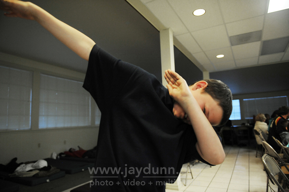Nathaniel Ashlin, 11, dabs for fun after dinner at the warming shelter in Salinas in early April, 2017. Nathaniel is with his mother Joan Sassman.