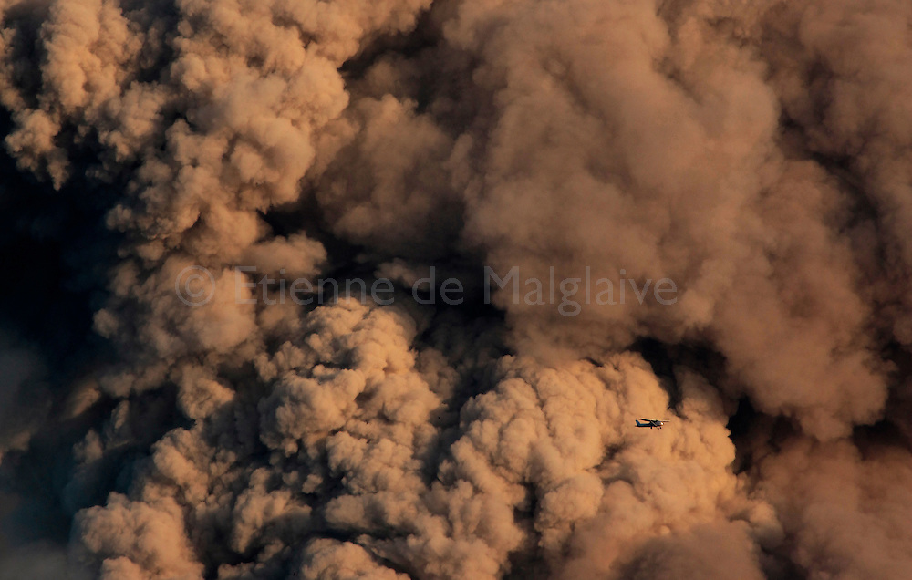 Tiny Cesna aircraft fly by the gigantic ash cloud from Iceland's Eyjafjallajokull during it's eruption, spewing tephra and ash cloud that drift toward continental Europe. Only pistons engines aircrafts can fly relatively close to the crater as their air filter prevent their engine from choking. Filterless turbine powered aircrafts and helicopters are not allowed to fly around the volcano. 10 May 2010. © Etienne de Malglaive.