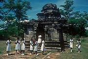 1980s Sri Lankan schoolgirls in clean white uniforms and visiting the ancient city of Polonnaruwa, stand alongside the Shiva Devale temple, on 12th Arpil 1980, at Polonnaruwa, Sri Lanka. Shiva Devale No 2 is the oldest structure in Polonnaruwa and dates from the brief Chola period, when the Indian invaders established the city. Built in the 11th century, this Hindu temple built entirely of stone. Within in the sanctum is a stone carved lingam or phallus, a symbol of Hindu god Diva. In front of the temple is the Nandi bull, God Shiva's vehicle. Polonnaruwa, Sri Lanka's splendid medieval capital was established as the first city of the land in the 11th Century, A.D. (Photo by Richard Baker / In Pictures via Getty Images)