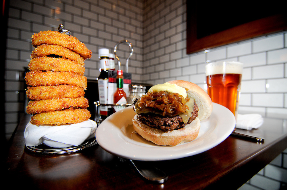 A burger, onion rings, and beer in a booth at 5 Napkin Burger in Boston, MA.