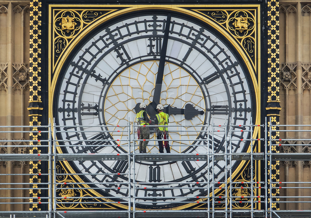 © Licensed to London News Pictures. 12/10/2017. London, UK. Scaffolders look at a clock face on Elizabeth Tower, known as Big Ben at Parliament. Scaffolding will reach a height of 96 meters when completed - the work is part of a three-year programme to conserve the Great Clock, the Elizabeth Tower and Big Ben. London, UK. Photo credit: Peter Macdiarmid/LNP