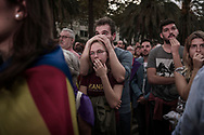 Pro- independence supporters react as they hear Catalan President Carles Puigdemont announce he will abide by the independence vote as they watch on big screens outside the Parliament of Catalunya as the Catalan President Carles Puigdemont speaks on October 10, 2017 in Barcelona, Spain