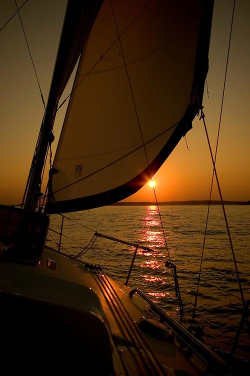 Sailboat sailing into the setting sun.