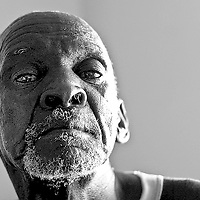 AIDS remains a very relevant issue in South Africa, with an estimated 40% of people suffereing from the epidemic. Here, a man poses for a picture while sitting in his room in an AIDS hospice. The hospice takes care of patients who show a variety of symptoms of the disease, but mainly provide a social support for the patients before they pass on.