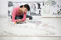 Businesswoman drawing on large paper on floor