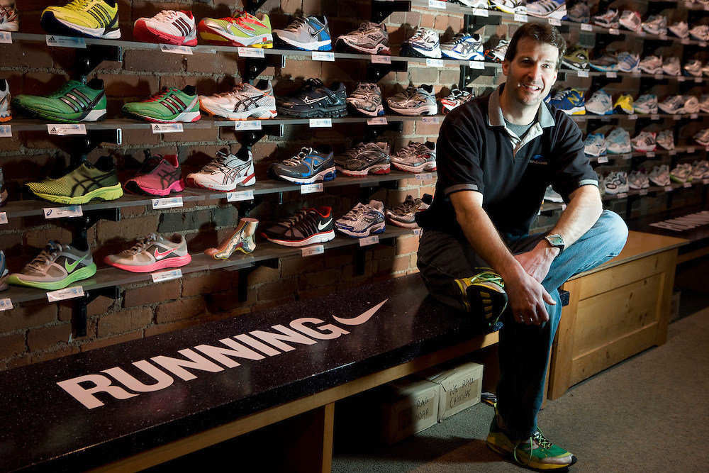(20110324, Boston, Massachusetts)..Shane O'Hara, manager of Marathon Sports in Boston, Massachusetts, sits in front of his store's lineup on Thursday, March 24, 2011.  Founded in 1975, Marathon Sports caters to high-performance endurance and track athletes, selling everything from custom-fit shoes to one-piece triathlon suits.  The Boston location, one of 6 Marathon Sports outlets in the greater Boston area, is located just feet from the finish line of the Boston Marathon on Boylston Street...Photo by Brooks Canaday.