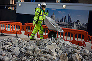 A workman tips broken up concrete on to a growing pile of construction rubble near an skyline illustration of the City of London.