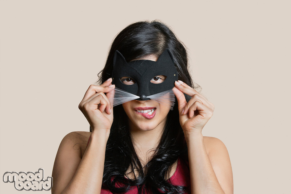 Portrait of a young woman wearing eye mask while biting lip over colored background