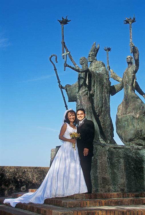 Couple posing for wedding photos at La Rogativa sculpture in Old San Juan, Puerto Rico.