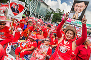 19 MAY 2013 - BANGKOK, THAILAND:    A Red Shirt holds up a photo of ousted and exiled Thai Prime Minister Thaksin Shinawatra during a Red Shirt rally in Ratchaprasong Intersection honoring Red Shirts killed by the Thai army in 2010. More than 85 people, most of them civilians, were killed during the Thai army crackdown against the Red Shirt protesters in April and May 2010. The Red Shirts were protesting against the government of Abhisit Vejjajiva, a member of the opposition who became Prime Minister after Thai courts ruled the Red Shirt supported government was unconstitutional. The protests rocked Bangkok from March 2010 until May 19, 2010 when Thai troops swept through the protest areas arresting hundreds. PHOTO BY JACK KURTZ