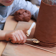 Boy working on clay during a pottery workshop for kids