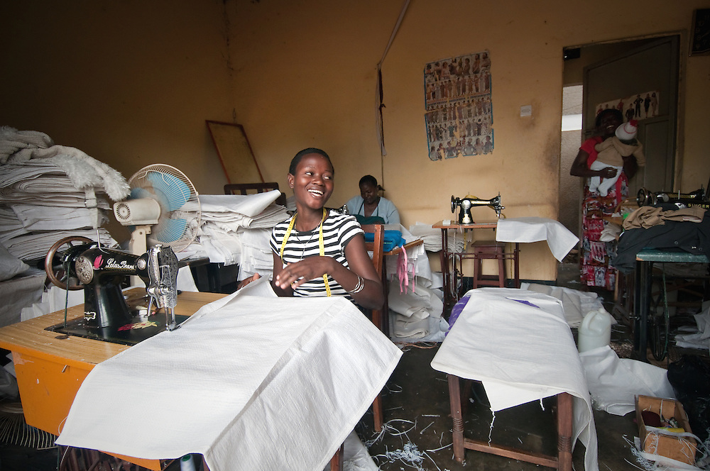 Women from low-income families sew grain sacks which will eventually be used as educational board games or large story charts for Mango Tree Enterprises. Mango Tree develops culturally relevant educational material and games for schools, grassroots educators, community health workers, governments and NGO's across East Africa. Their products are made mostly from locally available resources like grain sacks and bottle tops