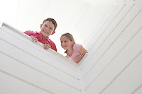 Young girl and boy looking over white wall view from below