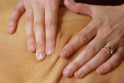 Closeup of physiotherapist massaging patient's back,