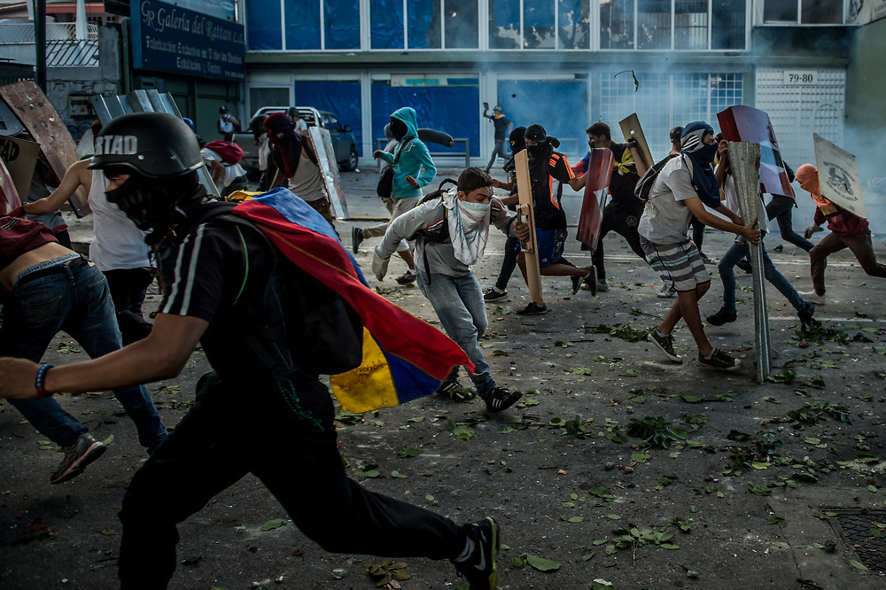 CARACAS, VENEZUELA - JULY 26, 2017: Members of La Resistencia flee as they are chased by soldiers shooting tear gas and rubber bullets at them, during an anti-government protest to demand that the National Constituent Assembly election scheduled for Sunday, July 30th be cancelled. The political opposition called for a 48 hour national strike on July 26th and 27th, and for their supporters to close businesses, not go to work, and instead create barricades to block off their streets.  Opposition controlled areas of the country were completely shut down.  The strike was called as part of the opposition's civil resistance movement - that began on April 1st, to protest against the Socialist government's attempt to elect a new assembly that will have the power to re-write the constitution, and their opposition to the Socialist's continued threats to Venezuelan Democracy.  PHOTO: Meridith Kohut for The New York Times