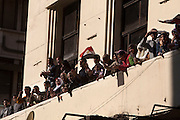Egyptians celebrate from a building balcony near Talat Harb Square February 12, 2011 in Cairo, Egypt. The day after the revolution toppled the regime of President Hosni Mubarak, Egyptians continued to celebrate and began to focus on rebuilding their country and society. (Photo by Scott Nelson)