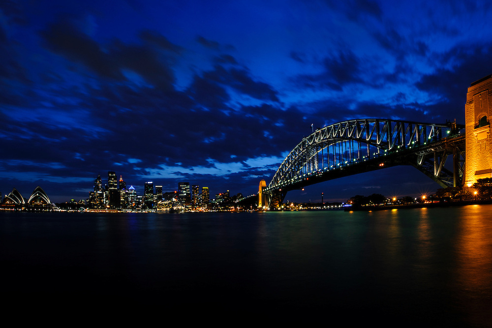 Sydney Harbour in Australia at dusk featuring the Sydney city skyline, the Harbour Bridge and the Sydney Opera House.