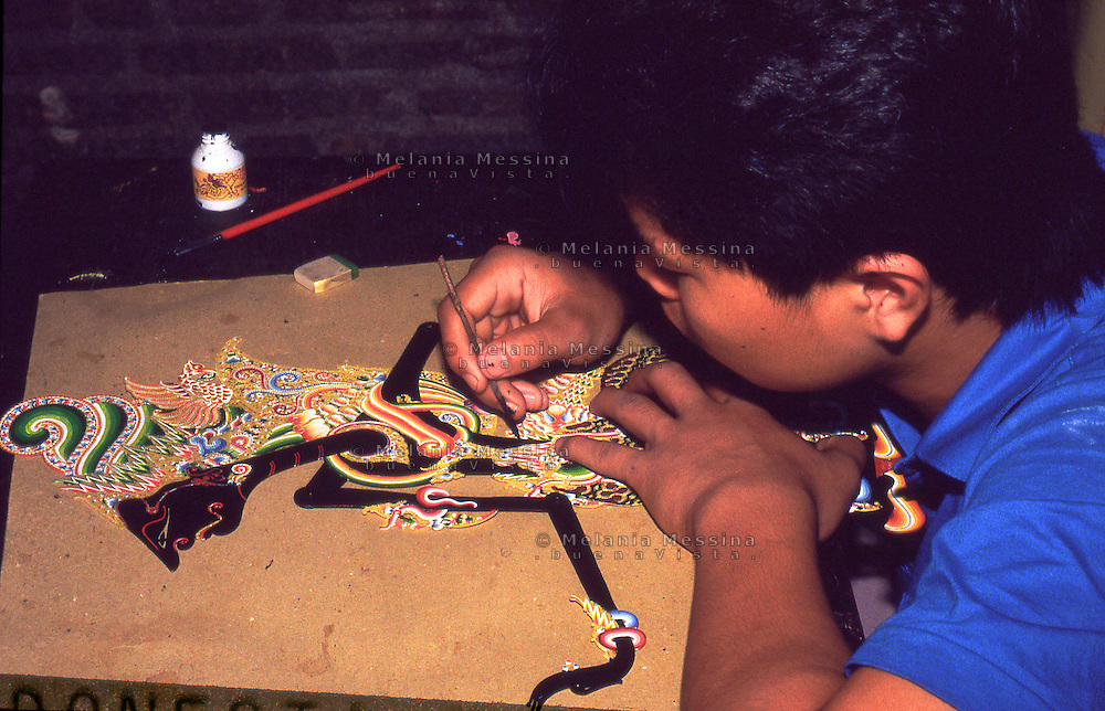Indonesia, Java island; Yogyakarta:Indonesian artisan decorates the puppets of the shadow theater .<br /> Indonesia; Giava, Yogyakarta: artigiano indonesiano decora una marionetta del teatro delle ombre.
