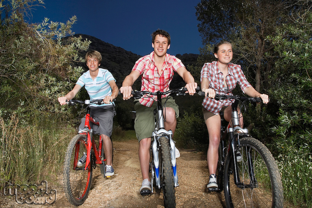 Teenage boys and girl (16-17 years) riding bikes on country road in evening