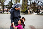"Sister Anna and two little girls. She came in 2008 to Lunik IX invited by the bishop and is working with The Salesians of Don Bosco Pastoral Mission, a Christian charity which operates in Lunik IX. She said about her work ""Having spent a certain period of time here, I now simply see myself as part of the community, the housing estate. They are mine and I am theirs and that's just the way it is."" Lunik IX has officially 6542 registered (12/2015) inhabitants and almost all of them are of Roma ethnicity."