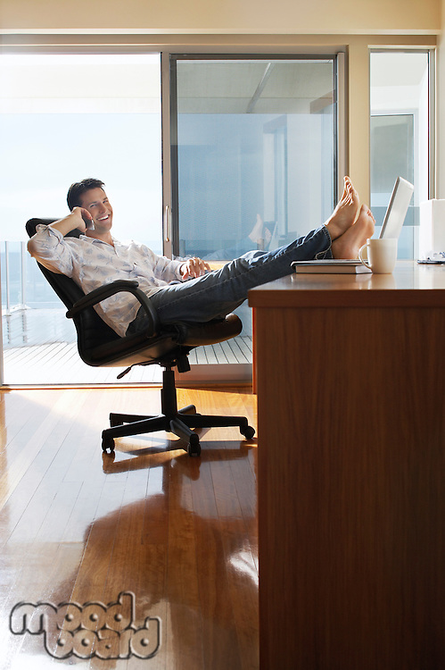 Man sitting in office with feet up on desk using mobile phone.