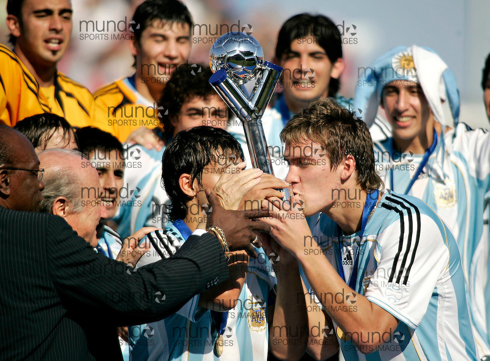 Argentina's Matias Cahais(R) and team captain Sergio Aguero kiss the  trophy following their victory at the FIFA U-20 World Cup on 22 July 2007 in Toronto, Ontario, Canada.  .AFP PHOTO/GEOFF ROBINS