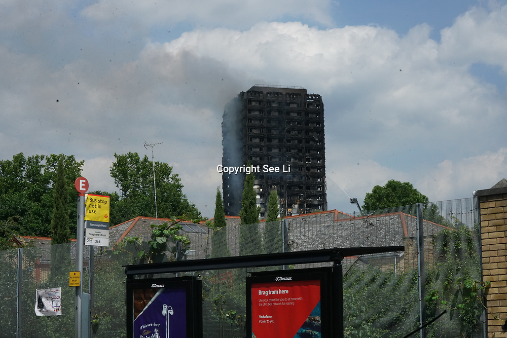 London, UK. 14th June, 2017. Fire fighters are trying to stop he fire in West London where the Grenfell Tower was blazing over night, the roads were closed due to the probability of building's collapse, London, UK.