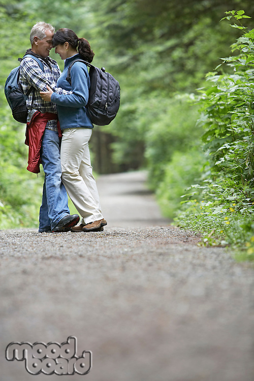 Couple embracing on forest road side view