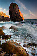 Near Roca Cape, at Malhada do Louriçal, a secluded small pebble beach, late afternoon light shines on one of the many seastacks