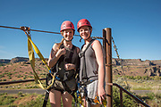Two young women smile while zip lining in the Snake River Canyon with Zip the Snake in Twin Falls, Idaho.
