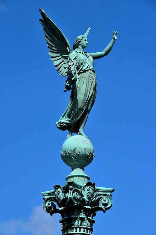 Winged Victoria Sculpture in Copenhagen, Denmark<br /> This statue standing on an orb atop the Ivar Huitfeldt Column is Victoria.  In Roman mythology, she was a winged goddess who symbolized victory over death during a war or battle. It seems appropriate that she towers over a monument to sailors who lost their life during the Great Northern War.  Artist Ferdinand Edvard Ring created the sculpture in 1886.