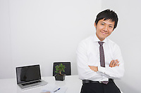 Portrait of happy mid adult businessman with arms crossed leaning on office desk