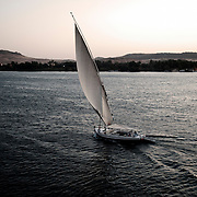 Felucca on River Nile and Qubbet el Hawa mountain with rock cut graves in the back . Aswan, Egypt.Africa.
