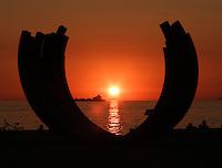 A sun set is framed by an art installation at English Bay beach in Vancouver, British Columbia in the early evening of a fall day.