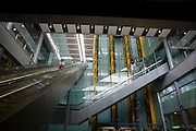 "A lone departing female passenger descends one of the 105 escalators in Terminal 5 of London's Heathrow Airport. Surrounded by the grand architecture created by the Richard Rogers Partnership (now Rogers Stirk Harbour and Partners), we look upwards at this vast atrium that takes passengers through 5A in departures to the outlying gates into Terminal 5B.Terminal 5 has the capacity to serve around 30 million passengers a year, taking £4.3bn to build. From writer Alain de Botton's book project ""A Week at the Airport: A Heathrow Diary"" (2009). ..."