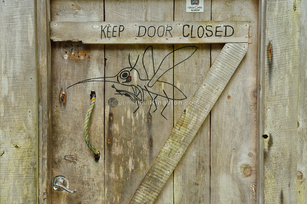 Carving of a giant mosquito holding a fork and knife on the door of a wooden cabin on SGang Gwaay or Anthony Island, Haida Gwaii, British Columbia.
