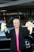 Portrait of cheerful female owner showing washcloth in car wash