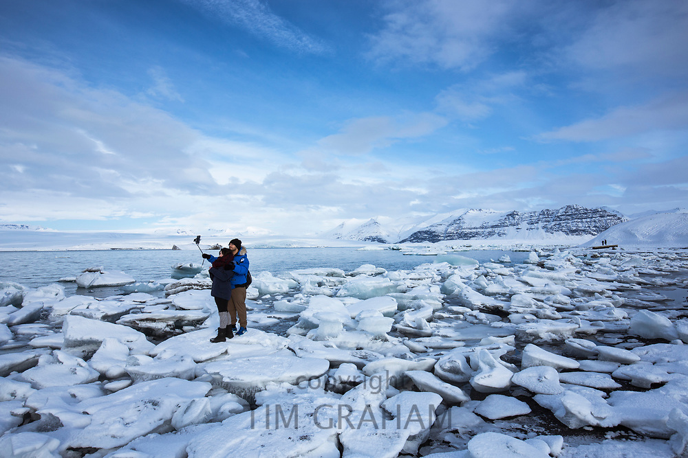 Tourists taking selfie photograph using smartphone for holiday photos at Jokulsarlon glacial lagoon, Vatnajokull National Park, South East Iceland