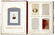 open vintage photo album from late 1800s with portraits and missing photographs