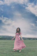 a woman in a pink dress is dancing on a meadow