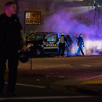NOVEMBER 9, 2016 - OAKLAND, CA: Police extinguish a fire to a squad car started by vandals after Anti-Trump protesters take the streets to express their sentiments over the victory of Donald Trump in the 2016 Presidential Election, in Oakland, California on November 9, 2016. (Photo by Philip Pacheco)