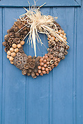 A wreath made of seed pods, nuts, and evergreen cones decorates the blue door of a summer cottage in southern Sweden.