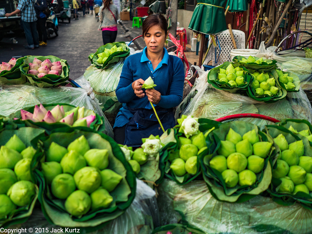"""21 DECEMBER 2015 - BANGKOK, THAILAND:  Selling lotus buds from a street side stand in Pak Khlong Talat, also called the Flower Market. The market has been a Bangkok landmark for more than 50 years and is the largest wholesale flower market in Bangkok. A recent renovation resulted in many stalls being closed to make room for chain restaurants to attract tourists. Now Bangkok city officials are threatening to evict sidewalk vendors who line the outside of the market. Evicting the sidewalk vendors is a part of a citywide effort to """"clean up"""" Bangkok.      PHOTO BY JACK KURTZ"""