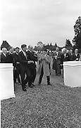 27/06/1963 - John F. Kennedy attends a garden party at Áras an Uachtaráin. The Minister for External Affairs, Frank Aiken, wrestles aside an eager young autograph hunter, although a smiling Kennedy appeared willing